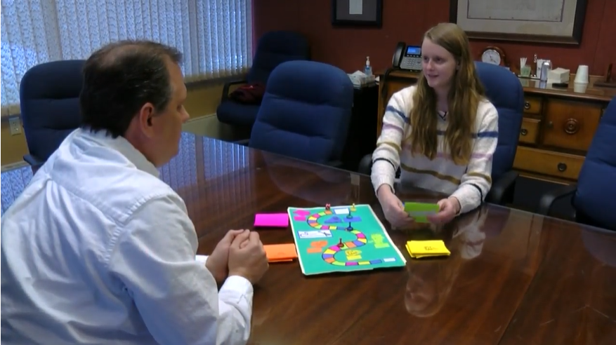 Picture of Appleton teen and the board game she created to teach financial literacy.