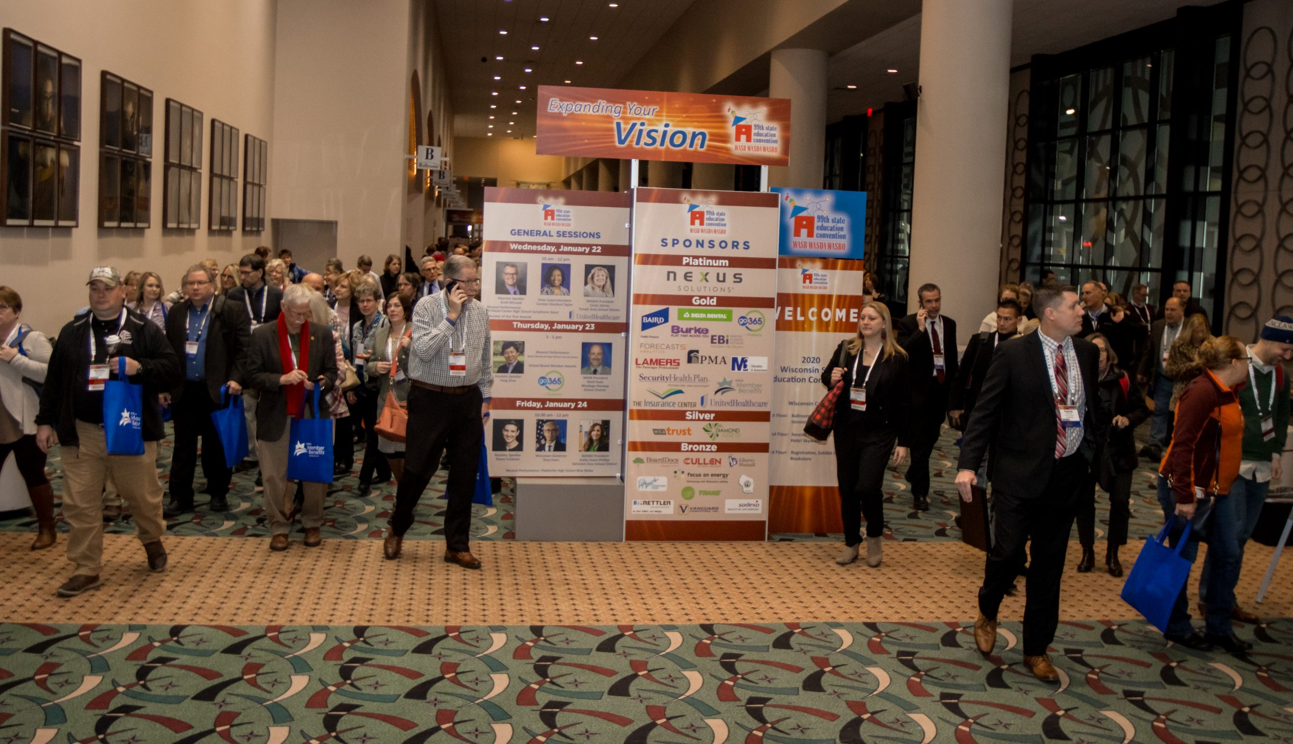 Attendees at the State Education Convention pass by a convention display.
