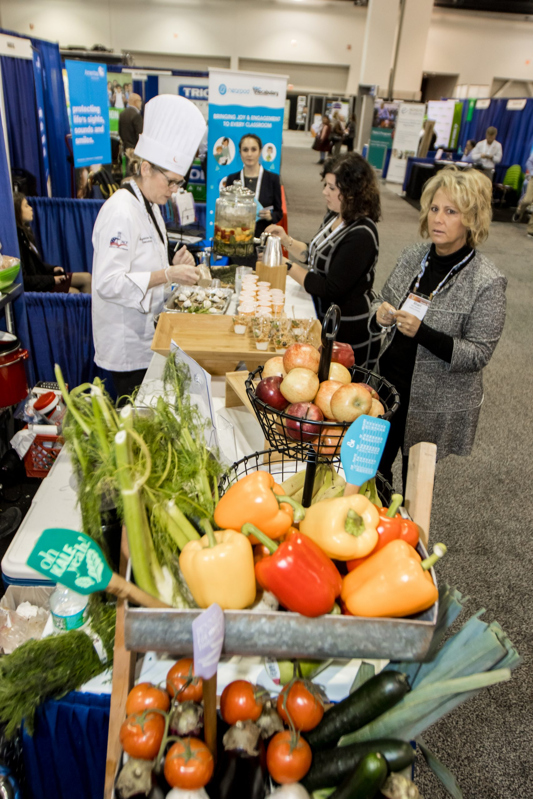 An Exhibit Hall presenter prepares food at the State Education Convention.