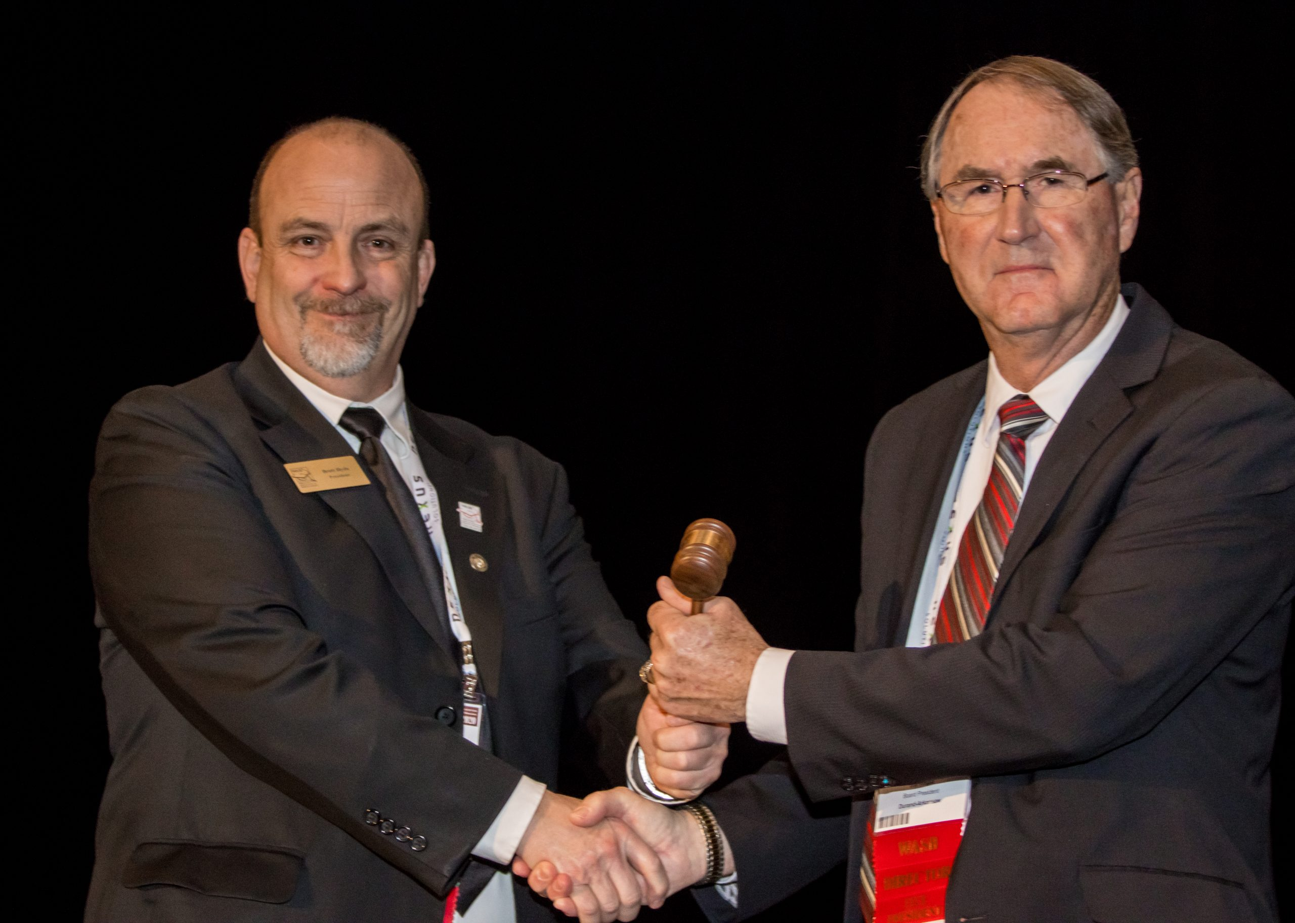 WASB Immediate Past President Brett Hyde, left, passes the gavel to incoming WASB President Bill Yingst, Sr.