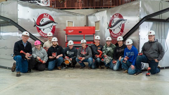Fond du Lac students pose with ice shanties they built