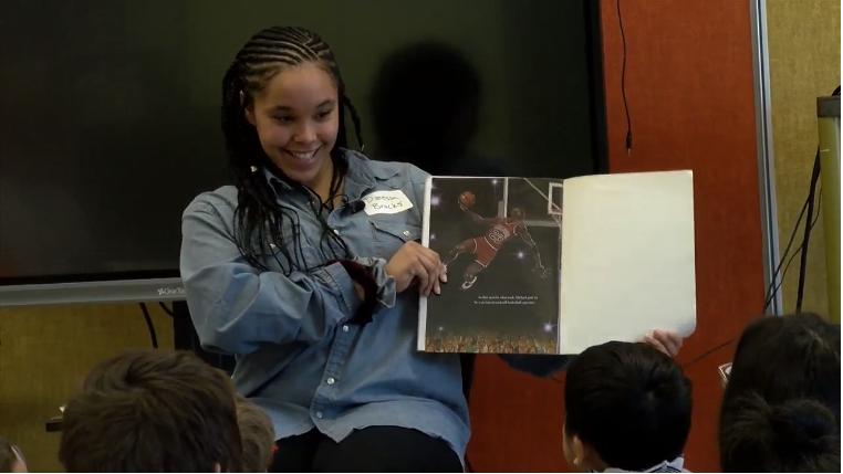 Student volunteer reads to children.