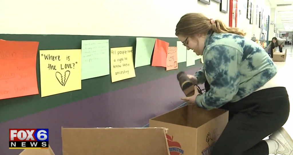 Student puts shoes collected in drive into box.