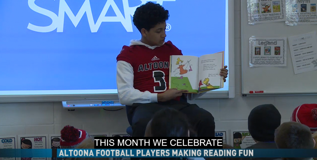 An Altoona football player reads to kids