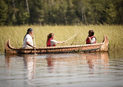 Students collect wild rice from a canoe