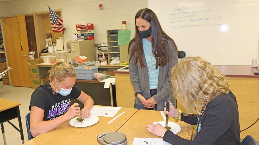 Teacher works with students